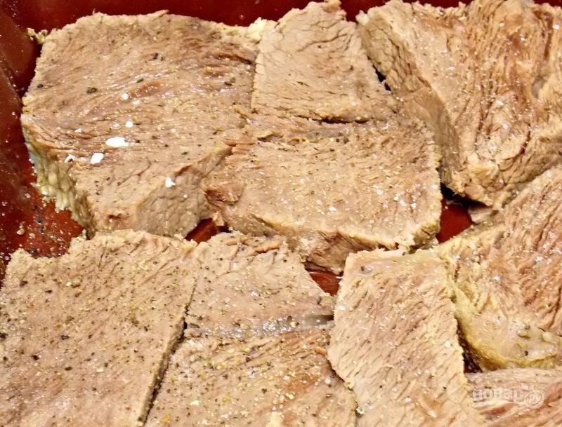 Нарежьте вареную говядину примерно на одинаковые кусочки и уложите в смазанную форму.