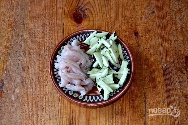 Нарежьте филе и баклажаны тонкими полосками. В сковороде разогрейте растительное масло и обжарьте на сильном огне курицу 4-5 минут, помешивая.