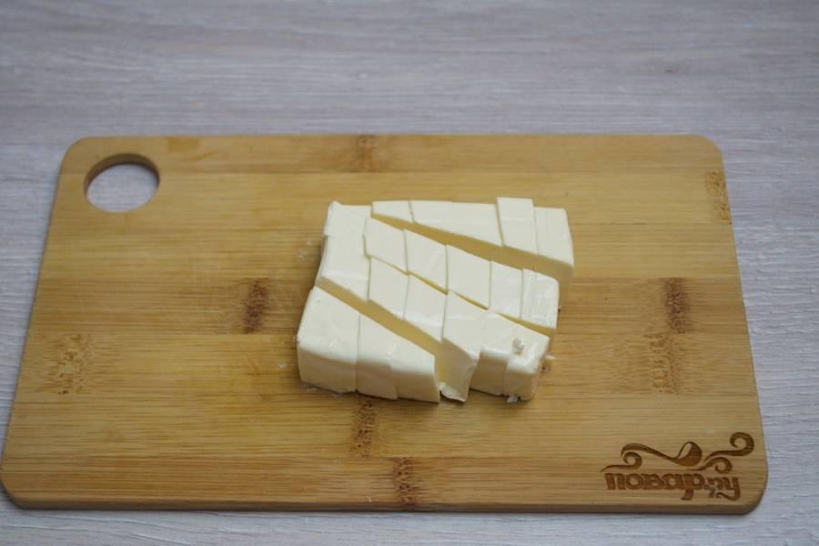 6.  Картофель варится 10-15 минут. Добавьте в бульон колбасу (без предварительной обжарки), овощную зажарку. Нарежьте плавленый сырок кубиками, добавьте его в бульон. Помешивая, дайте супу снова закипеть. Помешивайте суп до тех пор, пока плавленый сыр не растворится в жидкости полностью.