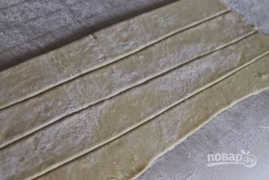 4.Раскатайте пласт слоеного теста и разрежьте его на тонкие полоски (около 1-2 см в ширину).