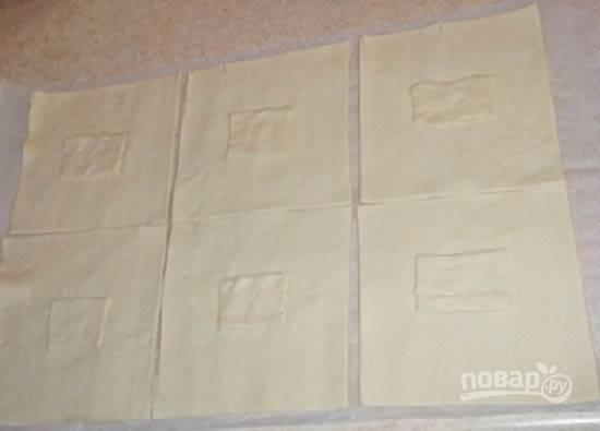 Отрежем от пласта теста небольшую полоску, примерно 4 см шириной. Оставшийся пласт делим на 6 частей. Полоску поделим на 6 кусочков и выложим их по центру каждого квадрата теста.
