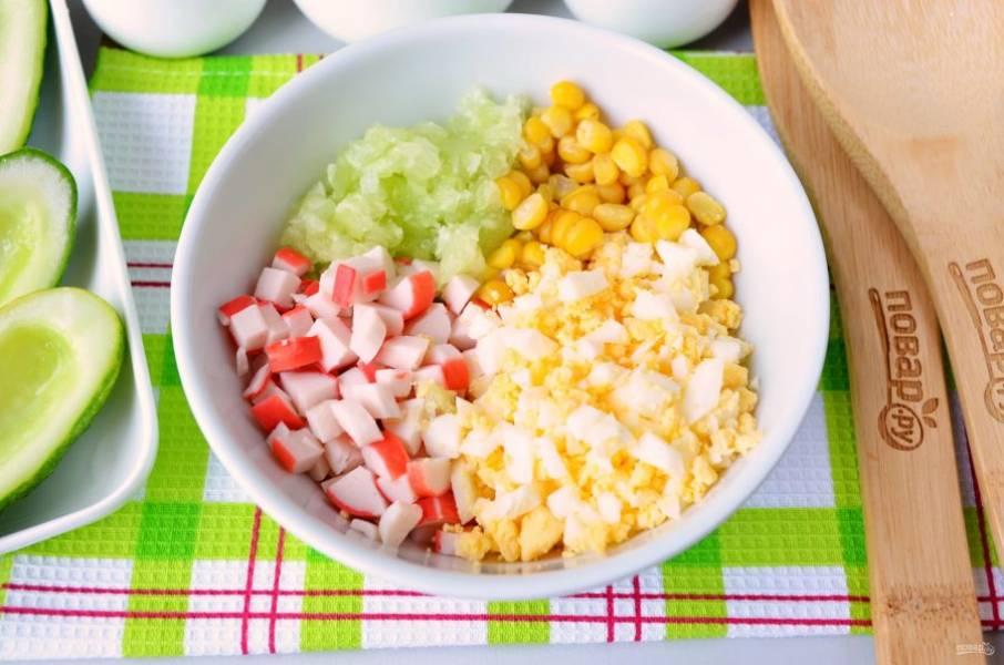 Порежьте мелко крабовые палочки, мякоть огурца, яйцо. Соедините в салатнике все ингредиенты.