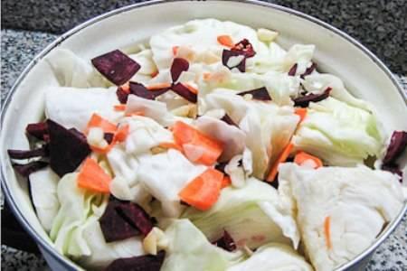 Затем укладываем овощи в подходящую кастрюлю. Слои капусты перекладываем морковью, свеклой и чесноком.