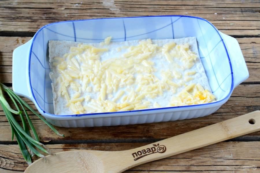 Дно формы смажьте сливочным маслом и положите первый лист лаваша. Положите на него ¼ всей начинки и разравняйте. Сверху накройте вторым листом лаваша и повторите процедуру. Обратите внимание, у нас получится 5 листов лаваша и 4 слоя сырной начинки. Верхний лист лаваша можно смазать взбитым яйцом, а можно оставить и так.
