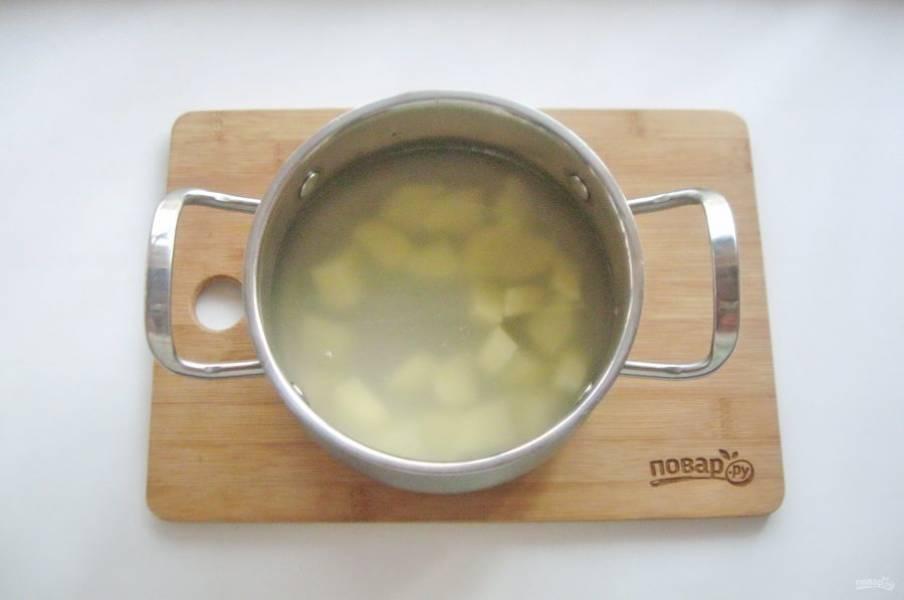 В кастрюлю налейте куриный бульон или воду. Добавьте нарезанный картофель.