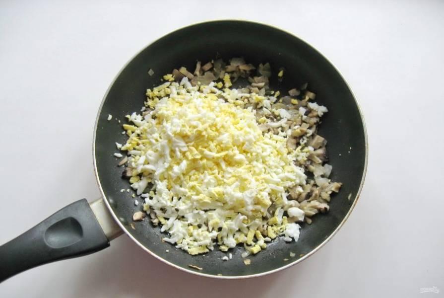 Яйца сварите вкрутую, охладите, очистите и натрите на терке. Добавьте к луку и грибам.