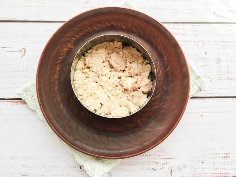 Поверх риса выложите печень трески, предварительно размяв ее вилкой.