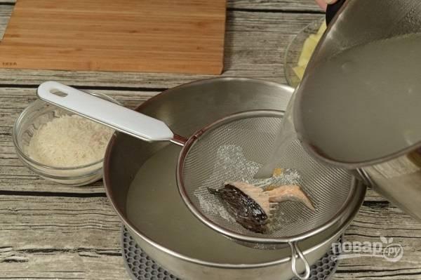 6. Бульон процедите, доведите до кипения. Выложите обжаренные овощи, картофель, рис. Посолите, добавьте специи и варите около 15-20 минут.  Приятного аппетита!