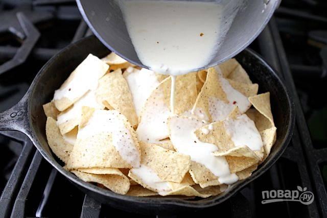 4. Выложите чипсы в сковороду. Залейте их соусом.
