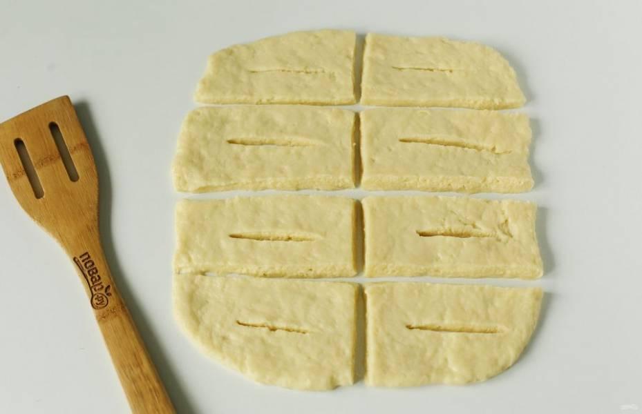Рабочую поверхность и скалку смажьте растительным маслом. Тесто разделите на 2 части и каждую часть поочередно раскатайте в форме прямоугольника, толщиной около 7-8 мм. Нарежьте тесто на полоски, примерно 3х6 см. В середине каждой получившейся полоски сделайте надрез как на фото.
