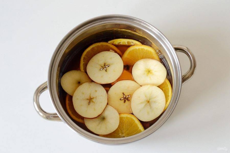 Добавьте апельсин и яблоко порезанные кружочками. Варите напиток еще 5-6 минут.