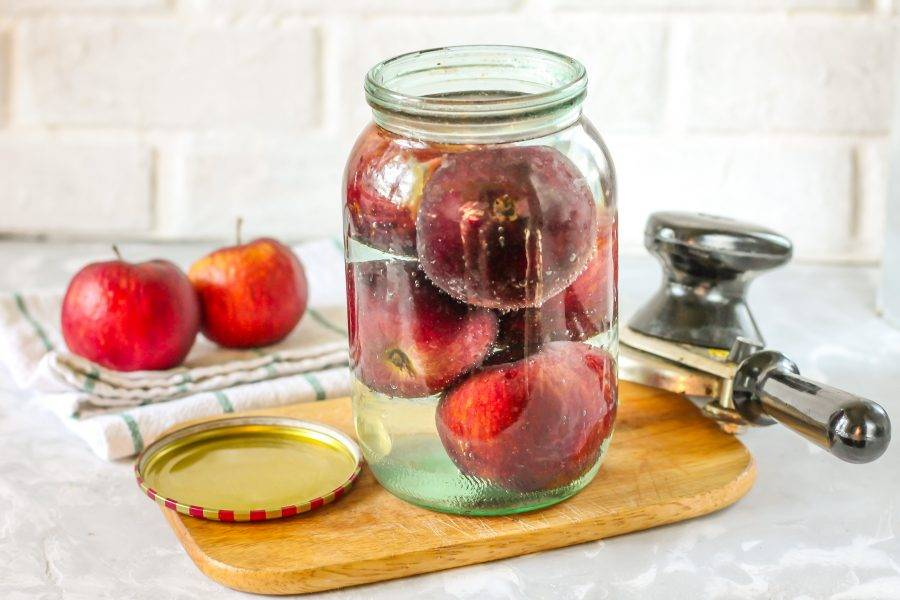 Выключите нагрев и влейте горячий сироп в банку с яблоками. Сразу же закройте с помощью закаточного ключа или закрутите горячими крышками по резьбе.