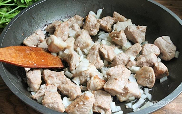 Как только выпарится жидкость, выделяемая мясом, добавляем измельченный репчатый лук. Жарим 5 минут, постоянно помешивая.