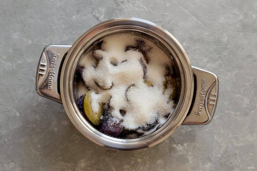 Переложите сливы в кастрюлю с толстым дном, затем насыпьте сахар. Налейте воду, капните ванильный сироп и доведите до кипения на среднем огне.