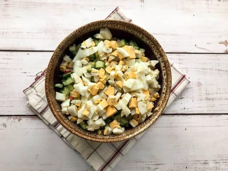 Вареные яйца очистите от скорлупы, нарежьте и высыпьте в тарелку.