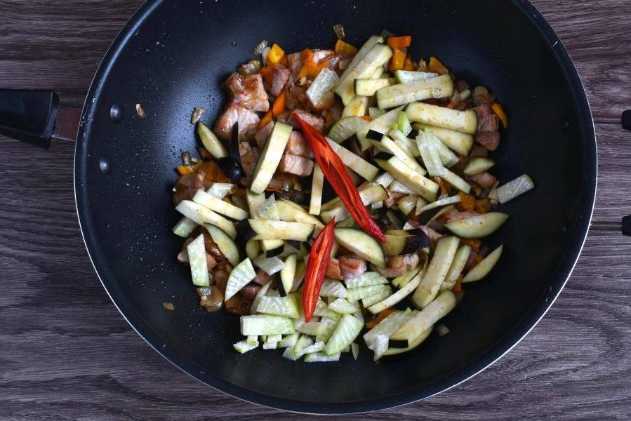 Добавьте брусочки баклажана и кубики редьки. Положите острый перчик, разрезав его пополам и по желанию удалив семена, чтобы суп был менее острым. Перемешайте и прогрейте пару минут.
