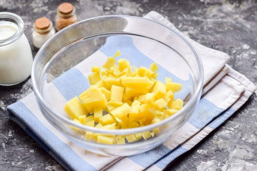 Картофель нарежьте небольшими кубиками, выложите в глубокую миску или кастрюлю.