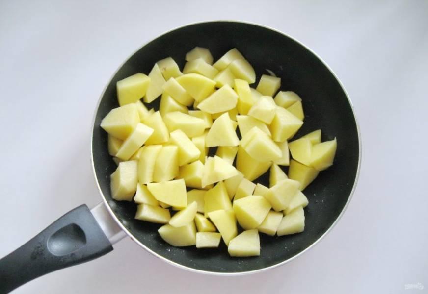 Картофель очистите, помойте и нарежьте не очень мелкими кубиками. Выложите в сковороду с подсолнечным маслом.