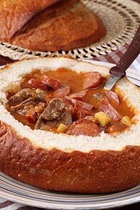 5. Когда овощи и грибы потушатся, добавляем немного томатной пасты и доводим до готовности. Выливаем наш суп в середину хлеба, посыпаем по вкусу зеленью и накрываем коркой. Подавать суп-гуляш в хлебе  в домашних условиях нужно горячим.
