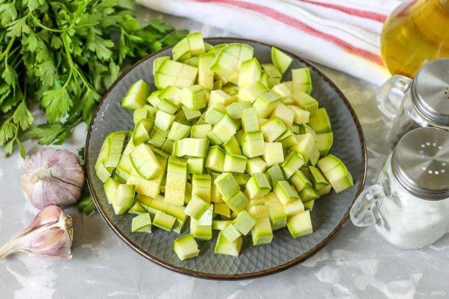 Промойте кабачки в воде, срежьте хвостики и нарежьте овощи кубиками. Для блюда выбирайте молоденькие кабачки без жесткой кожуры и семян внутри.