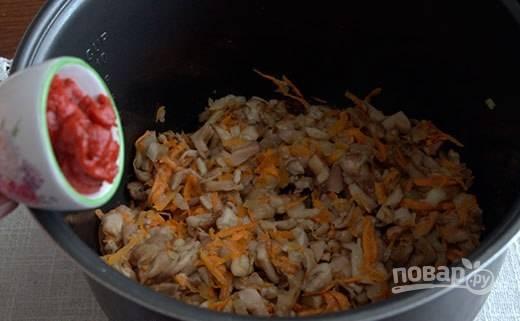 Затем в чашу мультиварки добавьте томатную пасту. Перемешайте.