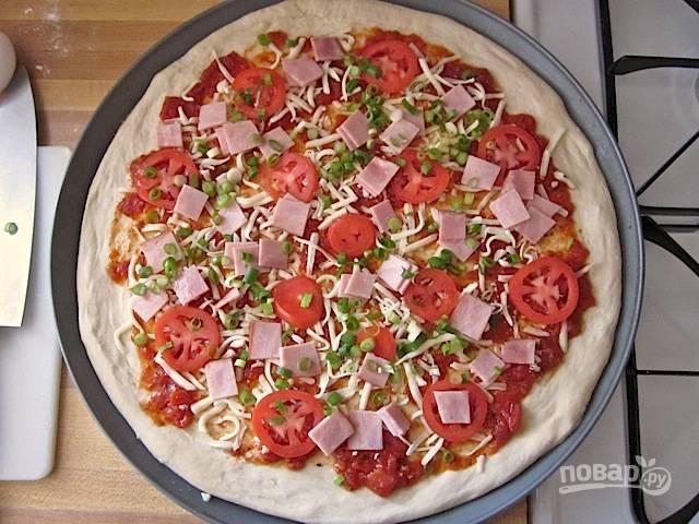 5.Посыпьте тесто половиной тертого сыра, положите сверху помидоры, ветчину и зеленый лук.