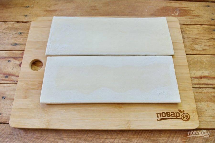 Слоеное тесто нужно разморозить до мягкого состояния, но не полностью. Вы должны иметь возможность раскатать его скалкой так, чтоб тесто не потрескалось на осколки.