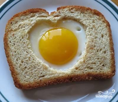 1. При помощи формочки в виде сердца для печенья или ножом вырежьте в хлебе отверстие. В сковороде разогрейте масло, обжарьте хлеб с одной стороны, переверните и вбейте яйцо. Посолите поперчите и обжарьте с другой стороны. Не забудьте обжарить и вырезанное сердце.