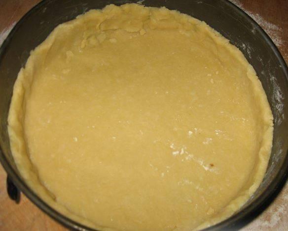 Через 30 минут достаньте тесто и раскатайте в пласт. Переложите его в смазанную маслом форму (22 см), сделайте бортики (3-4 см). Выпекайте в духовке 25 минут, температура 200 градусов.