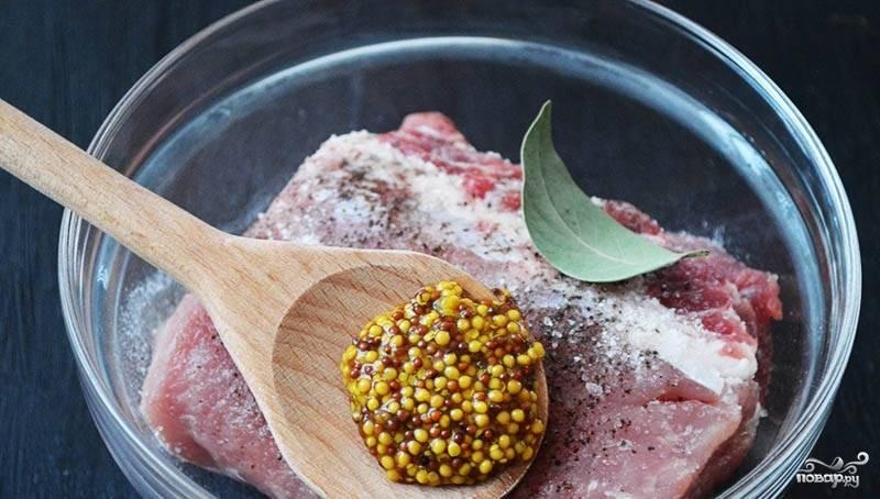 2.Помещаем мясо в миску, натираем его солью, молотым перцем, кладем горчицу и добавляем несколько лавровых листов.