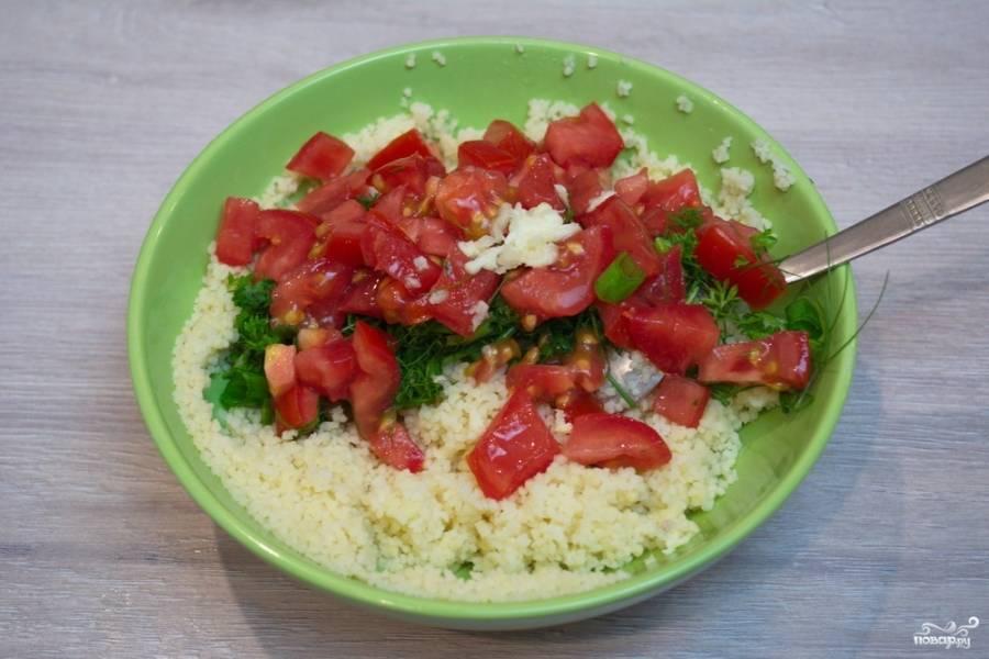 Кус-кус впитает воду. Нарезанную зелень и помидоры выложите в тарелку на кус-кус.  Выдавите немного чеснока. Перемешайте. Сделайте заправку. Смешайте немного растительного масла, соль, перец. Слегка взбейте вилочкой. Заправьте салат полученной заправкой и снова перемешайте.