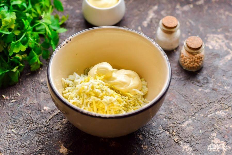 Куриные яйца очистите и сполосните. Натрите яйца на мелкой терке и смешайте с майонезом.
