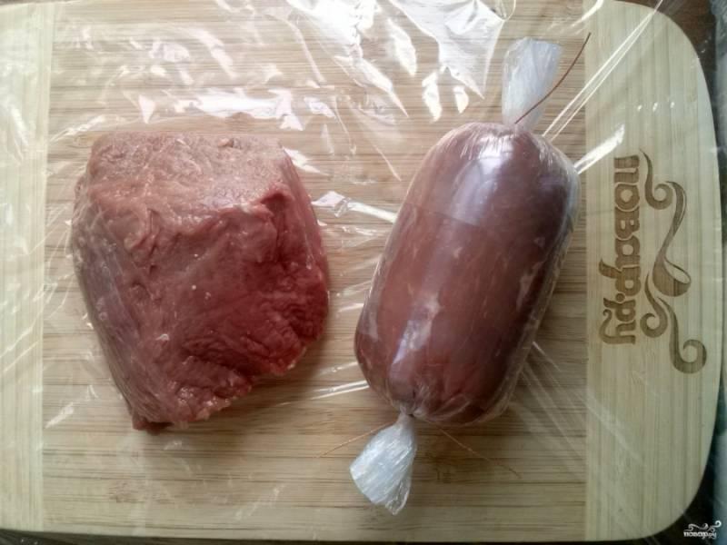 Филе телятины разрежьте пополам вдоль волокон. Заверните его плотно в несколько слоев пищевой пленки в виде колбаски, завяжите концы.