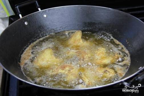 3. Раскаляем в глубокой сковороде масло, обжарим в нем крылышки до готовности. Откинем затем на салфетку, чтобы лишний жир стек.