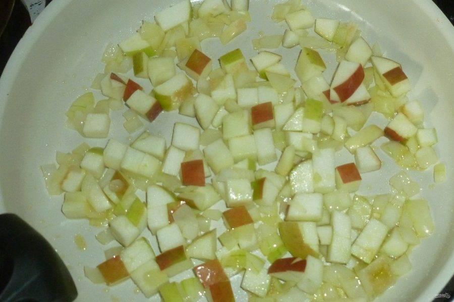 Яблоко нарежьте кубиками, лук мелко порубите. В сковороде разогрейте масло, обжарьте яблоко и лук.