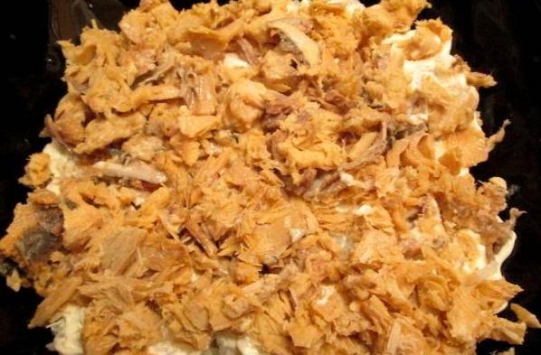 Горбушу разминаем вилочкой и кладем равномерно поверх риса.