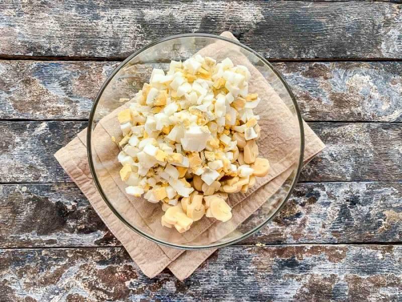 Яйца очистите от скорлупы, мелко нарежьте и добавьте к грибам.