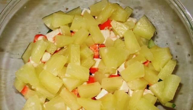 1. Яйца и курицу отварим, и пусть пока что остынут. Тем временем нарежем огурец, ананас и крабовые палочки кубиками. Помещаем в миску. Смазываем сверху майонезом.