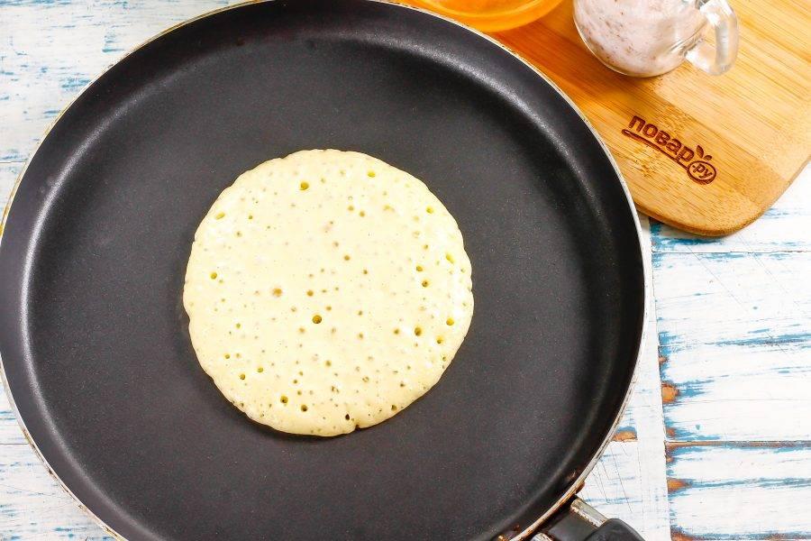 Блинную сковороду прогрейте на умеренном нагреве. Ее смазывать ничем не нужно. Влейте на середину емкости половину половника теста и обжарьте до того момента, когда пузыри на поверхности теста начнут лопаться.