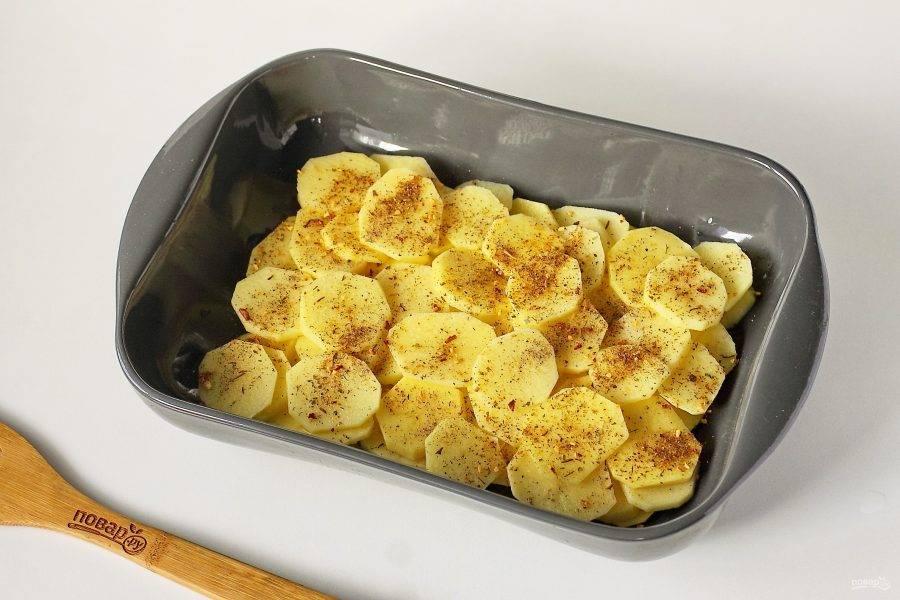 Форму для запекания смажьте маслом и выложите ровным слоем нарезанный картофель. Посолите слой и посыпьте специями. У меня смесь специй специально для картошки.
