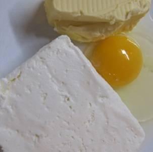 1. Первым делом нужно заняться тестом. В рецепт приготовления пирожков из творожного теста с яблоками используется яйцо, соль с разрыхлителем, творог и немного сливочного масла. Затем постепенно добавляйте просеянную муку. Ее количество зависит от жидкости основы - размера яйца и влажности творога.