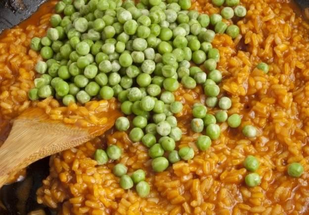 В почти готовы рис выкладываем зеленый горошек и оставшееся сливочное масло, солим все по вкусу и перемешиваем.