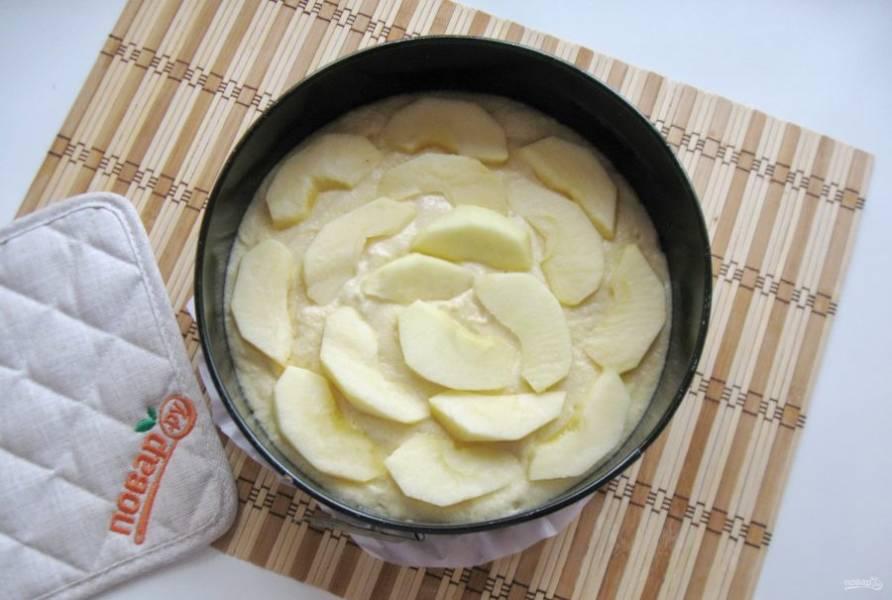 Выложите тесто в форму для выпечки с пекарской бумагой. Яблоки помойте, очистите. Удалите сердцевину и нарежьте дольками. Выложите яблоки на тесто.
