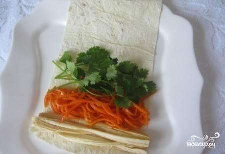 На каждую полоску лаваша выложите немного корейской морковки, зелени и сыра сулугуни. Если вы любите острое, то можете поперчить ингредиенты. Солить не нужно, так как сыр сулугуни и так достаточно соленый.