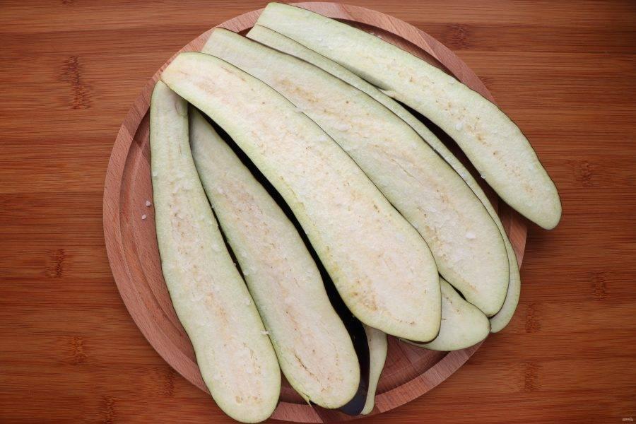 Баклажаны нарежьте длинными полосками толщиной в 1 см, посыпьте солью и оставьте на 30 минут. Затем смойте соль, просушите баклажаны и запекайте, смазав с обеих сторон оливковым маслом, в духовке под грилем около 10 минут. Один раз переверните.