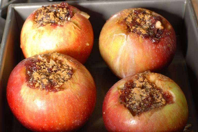 """Вырезаем у яблок сердцевину, удаляем семена, """"начиняем"""" их ягодами клюквы. Затем сбрызгиваем винным уксусом и обильно посыпаем сахарным песком."""