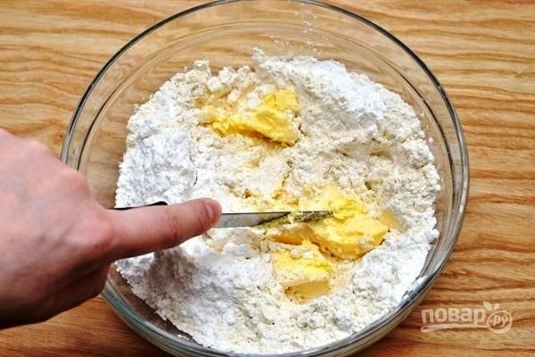 В глубокую миску просейте всю муку. Добавьте к ней масло, нарезанное кубиками, пудру и соль.