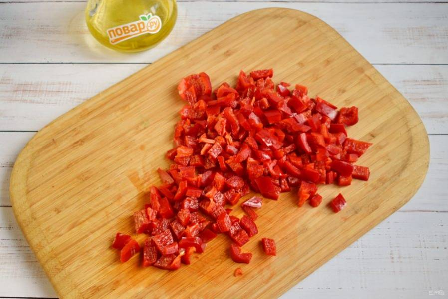Сладкий перец разрежьте пополам, удалите семена, нарежьте кубиками.