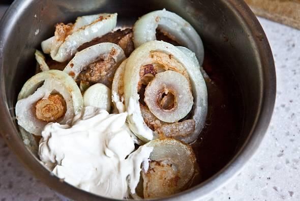 8. Печень и лук сложить в сотейник и добавить сметану. Влить на дно немного воды и отправить на огонь.