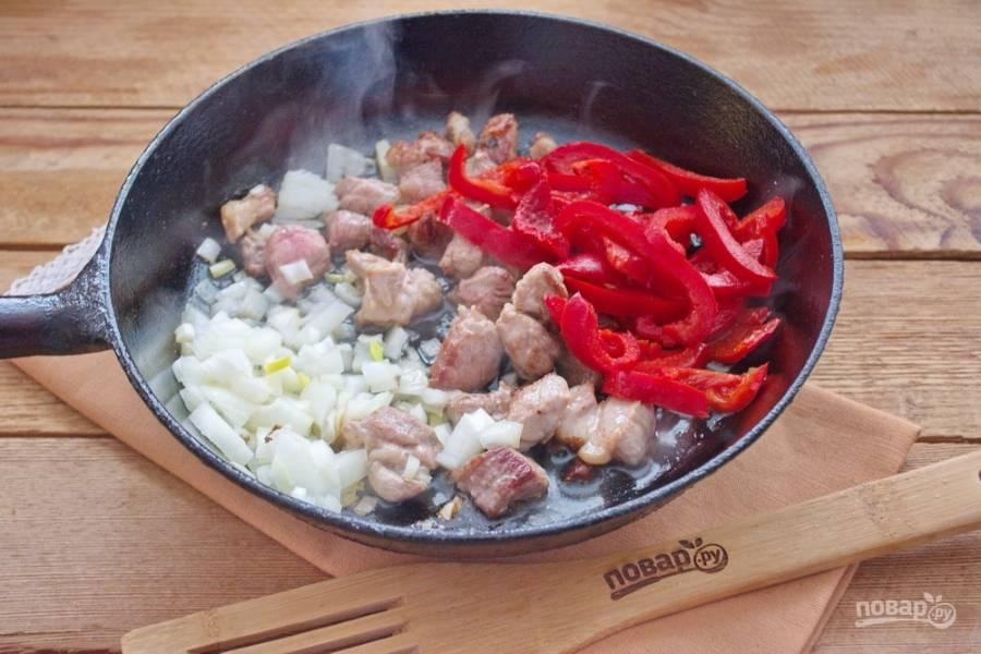 На растительном масле обжарьте нарезанное мясо.  Можно под крышкой. Когда на мясе появится румяная корочка, добавьте нарезанный репчатый лук и болгарский перец.
